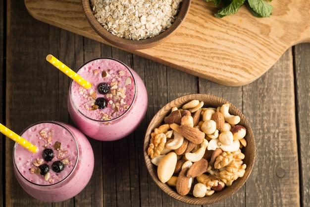 Glazen bessen smoothie met noten, munt, bosbessen, frambozen en yoghurt op houten tafel. gewichtsverlies en dieet. Premium Foto