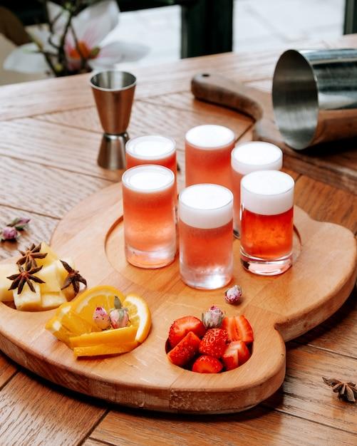 Glazen bier met schuim en gesneden fruit op het bord Gratis Foto