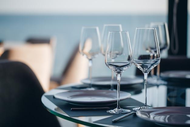 Glazen, bloemvork, mes geserveerd voor het diner in restaurant met gezellig interieur Premium Foto