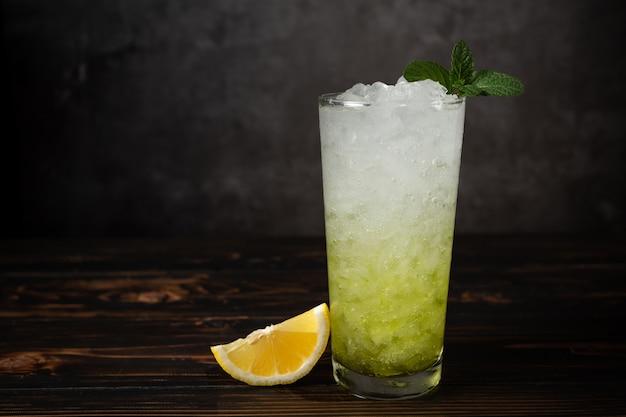 Glazen citroensap met ijs en verse munt op houten lijst. Gratis Foto