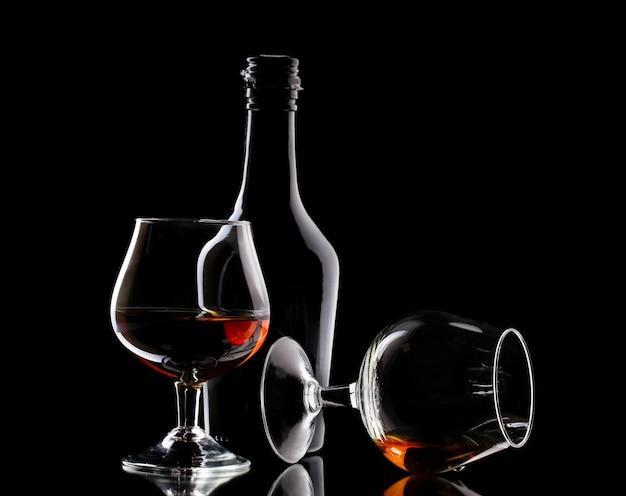 Glazen cognac en fles op zwarte lijst Premium Foto