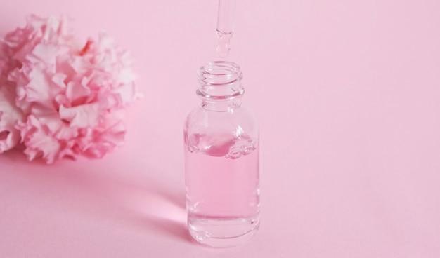 Glazen druppelflesje met olie. fles met een cosmetische pipet. hydraterende cosmetica tegen veroudering. huid- en lichaamsverzorging. roze olie essentie bloemproduct. Premium Foto