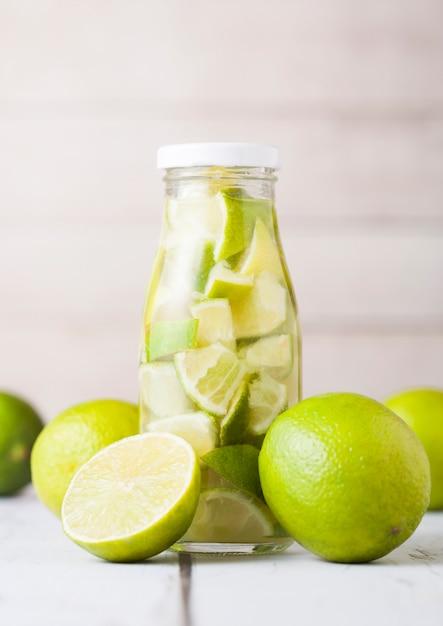 Glazen fles limoen nog fruitwater met fruit Premium Foto
