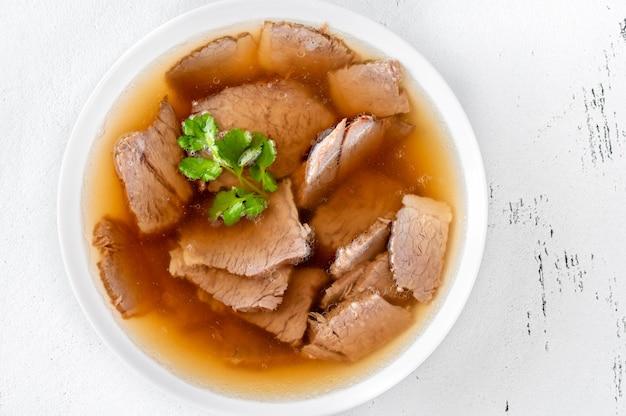 Glazen kom rundvlees bot bouillon met vlees op witte tafel Premium Foto