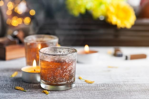 Glazen met aangestoken kaarsen en theepot Premium Foto