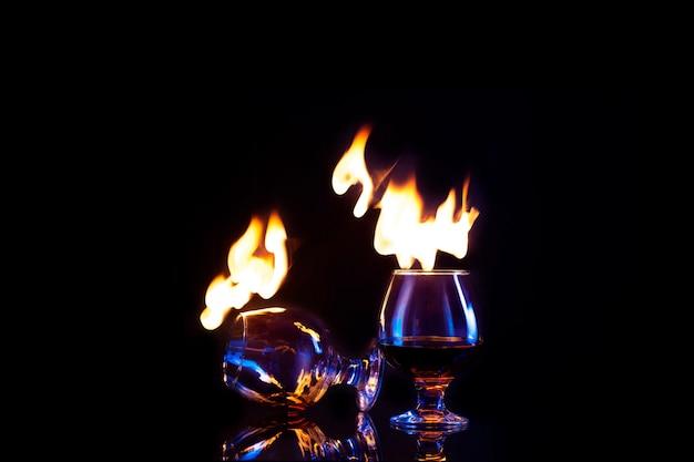 Glazen met brandende alcohol op donker Premium Foto