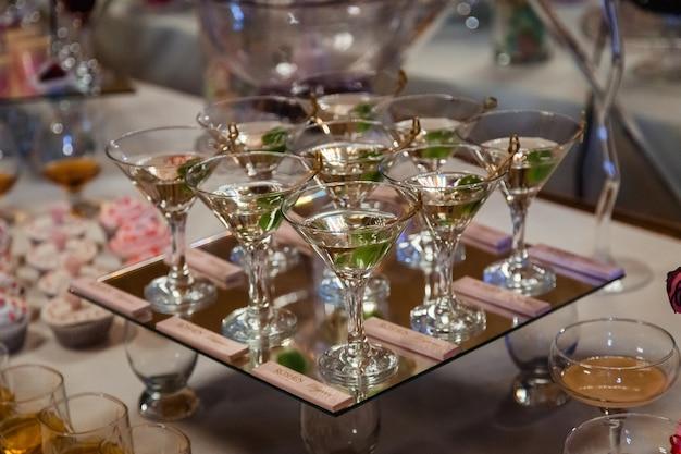 Glazen met martini en groene olijven staan op spiegelblad Gratis Foto