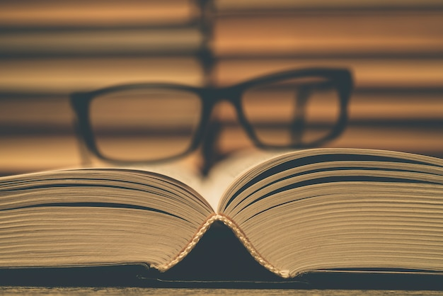 Glazen op de achtergrond van boeken. symbool van kennis, wetenschap, studie, wijsheid. Premium Foto