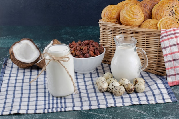 Glazen pot met melk, gedroogde dadels en kwarteleitjes op marmeren tafel. Gratis Foto