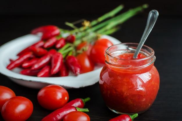Glazen pot tomatensaus met verse ingrediënten Premium Foto