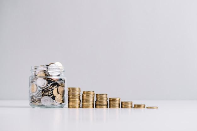 Glazen pot vol geld voor afnemende gestapelde munten Premium Foto
