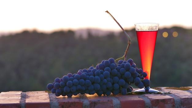 Glazen rode wijn met zwarte druiven op de zonsondergang Premium Foto
