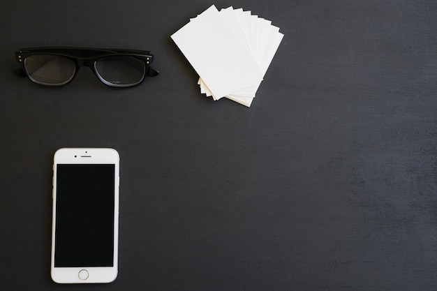 Glazen, telefoon en visitekaartjes op het bureau Gratis Foto