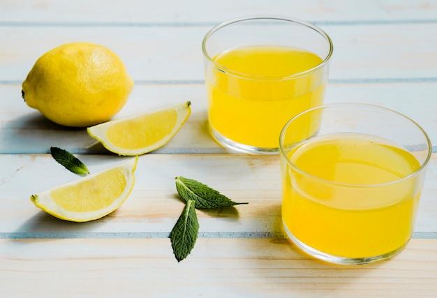 Glazen verfrissende gele drank dichtbij citroen en munt Gratis Foto