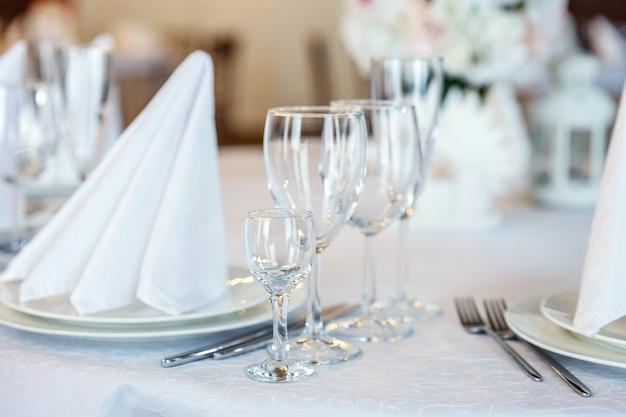 Glazen, vork, mes, servet gevouwen in piramide, geserveerd voor het diner in het restaurant Premium Foto