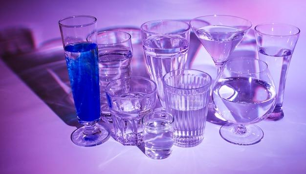 Glazen water met blauwe cocktail op gekleurde achtergrond Gratis Foto