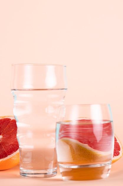 Glazen water met half rode sinaasappels Gratis Foto