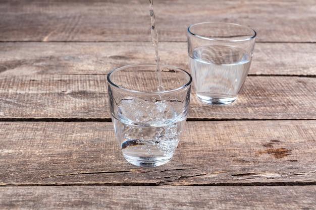 Glazen water op een houten lijst. Premium Foto