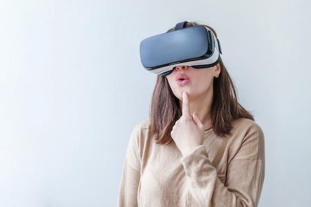 Glimlach jonge vrouw die gebruikend de virtuele hoofdtelefoon van de de glazenhelm van werkelijkheidsvr op wit dragen. smartphone gebruikt met virtual reality-bril. technologie, simulatie, hi-tech, videogameconcept. Premium Foto