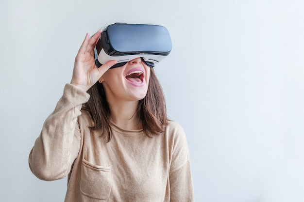 Glimlach jonge vrouw die gebruikend de virtuele hoofdtelefoon van de de glazenhelm van werkelijkheidsvr op witte achtergrond dragen. smartphone gebruikt met virtual reality-bril. technologie, simulatie, hi-tech, videogameconcept. Premium Foto