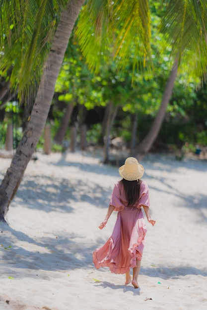 Glimlach van de portret de jonge aziatische vrouw gelukkig rond strand overzeese oceaan met kokosnotenpalm voor vakantievakantie Gratis Foto