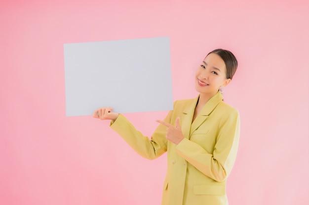 Glimlach van de portret de mooie jonge aziatische bedrijfsvrouw met lege witte aanplakbordkaart op kleur Gratis Foto