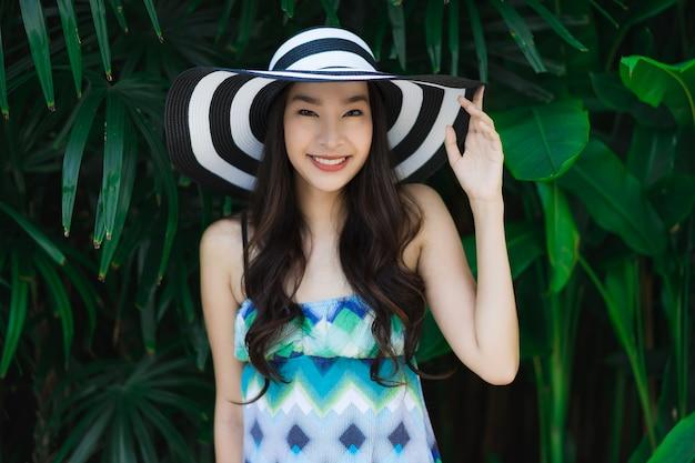 Glimlach van de portret de mooie jonge aziatische vrouw en gelukkige rond openluchttuin Gratis Foto