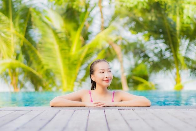 Glimlach van de portret ontspant de mooie jonge aziatische vrouw rond openluchtzwembad in resorthotel op de reis van de vakantiereis Gratis Foto