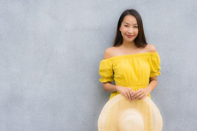 Glimlach van portret de mooie aziatische vrouwen gelukkig met concrete achtergrond Gratis Foto