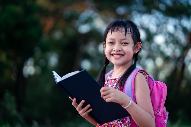 Glimlach weinig school meisje leesboek met rugzak. terug naar school concept Premium Foto