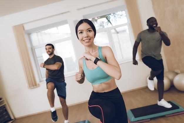 Glimlachatleten zijn bezig met fitness in de moderne sportschool. Premium Foto