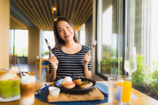 Glimlachen de portret mooie jonge aziatische vrouwen gelukkig in restaurant en koffiewinkelkoffie Gratis Foto
