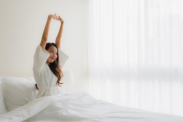 Glimlachen de portret mooie jonge aziatische vrouwen gelukkig op bed Gratis Foto