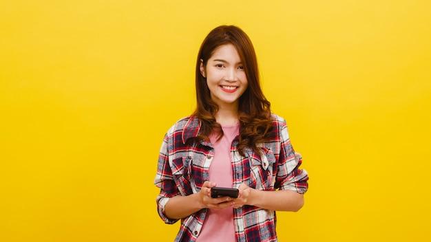 Glimlachend aanbiddelijk aziatisch wijfje die telefoon met positieve uitdrukking gebruiken, breed glimlachen, gekleed in vrijetijdskleding en camera over gele muur bekijken. de gelukkige aanbiddelijke blije vrouw verheugt zich succes. Gratis Foto