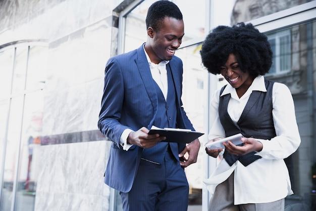 Glimlachend afrikaans jong zakenman en onderneemsterholdingsklembord en digitale tablet Gratis Foto