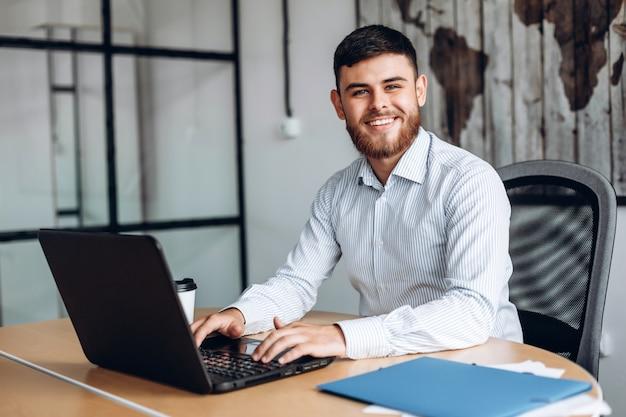 Glimlachend, bebaarde man aan het werk op computer in kantoor Premium Foto