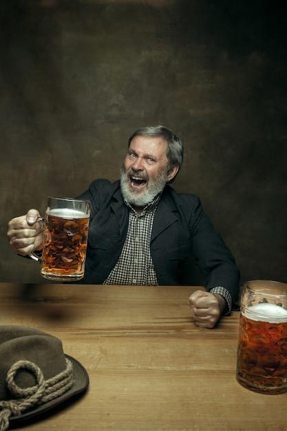 Glimlachend bebaarde man bier drinken in pub Gratis Foto