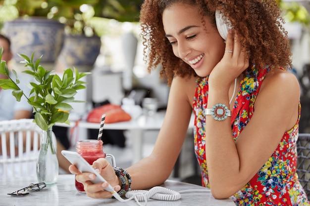 Glimlachend blij donkere vrouwelijke model besteedt vrije tijd op terras, maakt gebruik van moderne technologieën voor het luisteren naar favoriete muziek via koptelefoon Gratis Foto