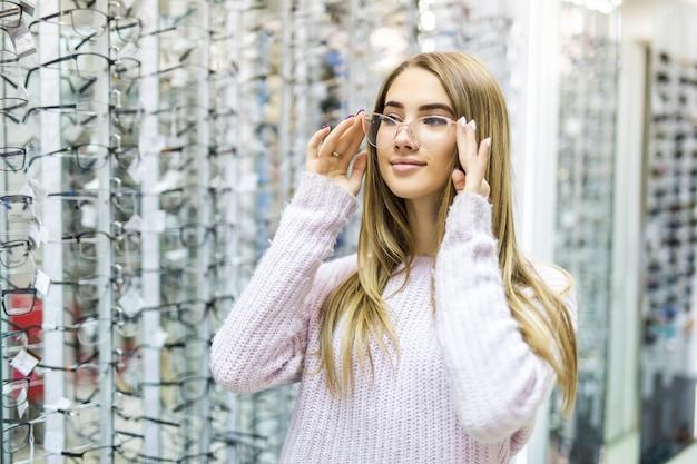 Glimlachend blond meisje in witte trui kies nieuwe medische bril in professionele winkel Gratis Foto