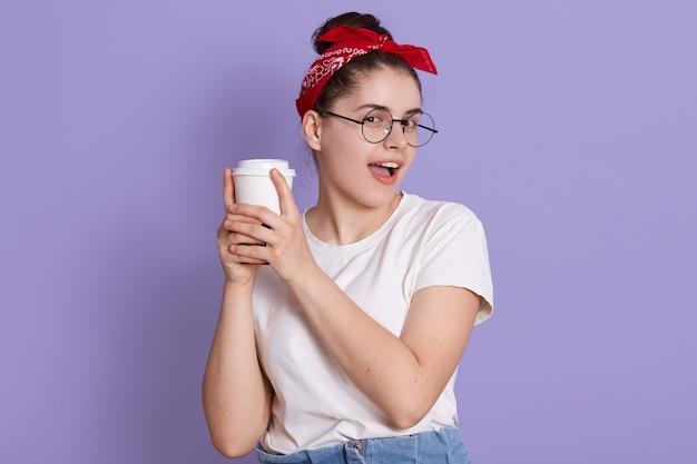Glimlachend brunette meisje in wit casual t-shirt met kopje koffie geïsoleerd over lila ruimte, camera kijken, houdt mond geopend Gratis Foto