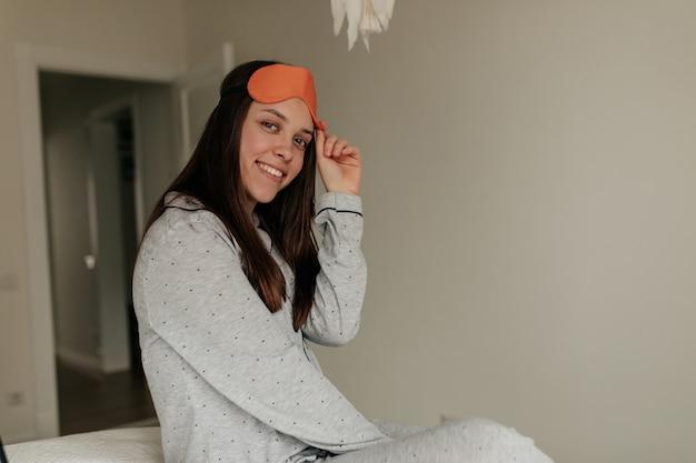 Glimlachend charmant meisje zwak thuis in haar moderne witte kamer met pyjama's en slaapmasker, ogen openen en raam kijken. Gratis Foto