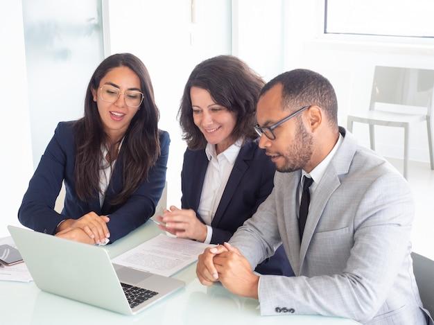 Glimlachend commercieel team dat laptop met behulp van Gratis Foto