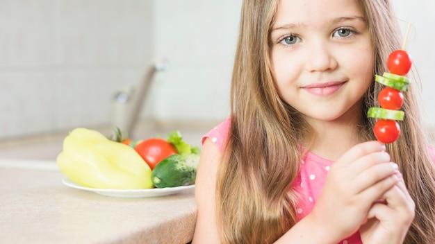 Glimlachend de saladevleespen van de meisjeholding ter beschikking Gratis Foto