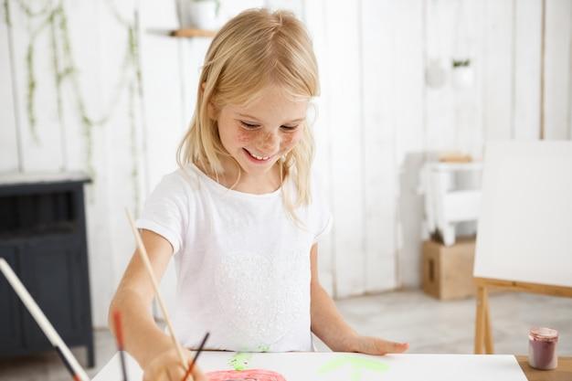 Glimlachend en vrolijk, vol vreugde kind met blond haar en sproeten met penseel in haar hand en ambitieus schilderij in de kunstkamer. Gratis Foto