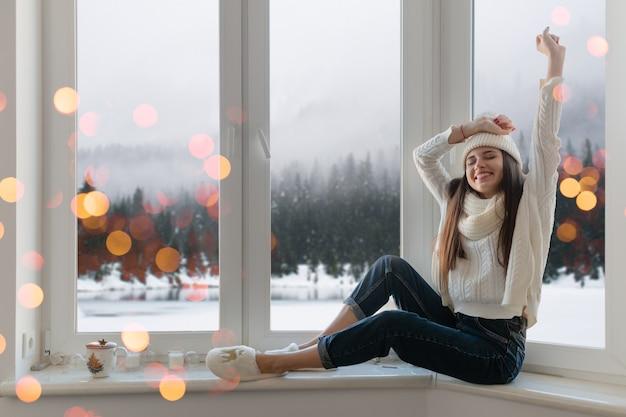 Glimlachend gelukkig jonge aantrekkelijke vrouw in stijlvolle witte gebreide trui, sjaal en muts om thuis te zitten op de vensterbank met kerstmis plezier hand in hand omhoog, winter bos achtergrond weergave, lichten bokeh Gratis Foto