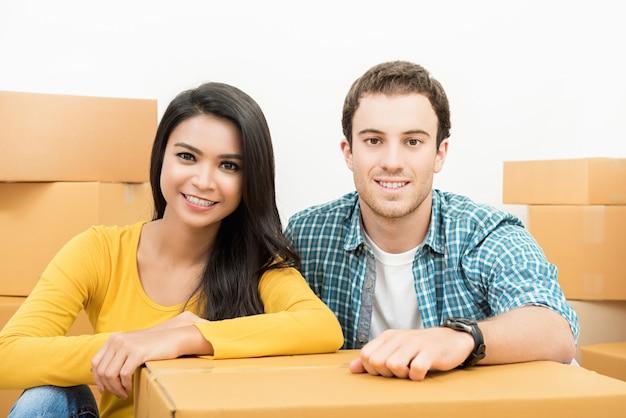 Glimlachend gelukkig paar tussen verschillende rassen die enkel zich in nieuw huis bewegen Premium Foto