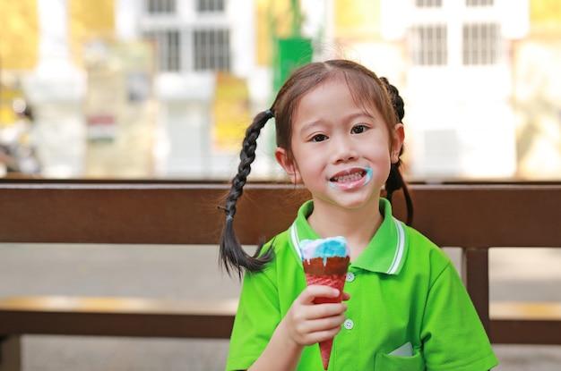 Glimlachend geniet weinig aziatisch jong geitjemeisje van het eten van roomijskegel met vlekken rond haar mond. Premium Foto