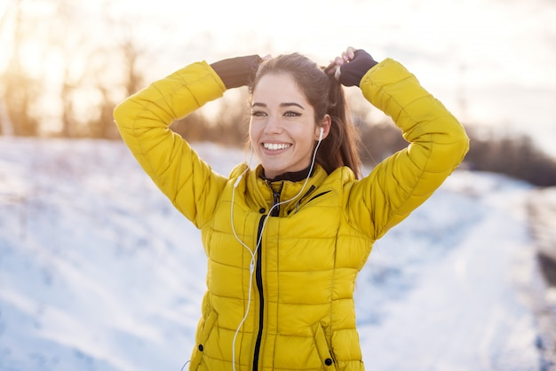 Glimlachend hardwerkende fitness meisje met oortelefoons in wintersportkleding koppelverkoop een paardenstaart buiten in de sneeuw natuur. Premium Foto