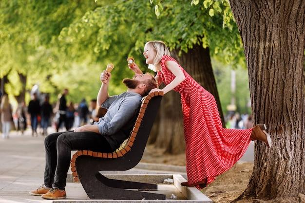 Glimlachend hipsterspaar die pret hebben en roomijs in de stad eten. stijlvolle jonge man met baard zit op een houten bank en blonde vrouw in rode jurk vrouw dwazen rond en speelt met hem Premium Foto