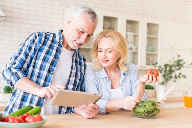 Glimlachend hoger paar die digitale tablet voor het voorbereiden van het voedsel in de keuken bekijken Gratis Foto